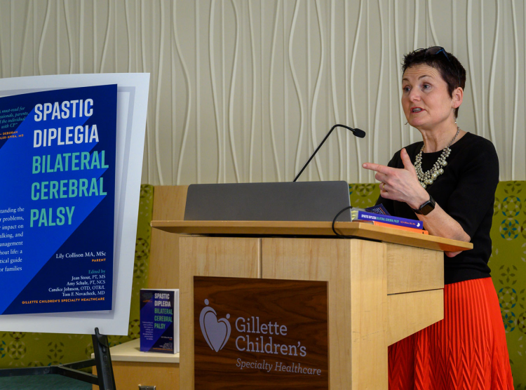 Lily Collison, author of the Gillette Press book about Spastic Diplegia, speaks at a podium at the launch event