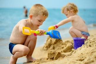 Two little kids playing in sand on the beach