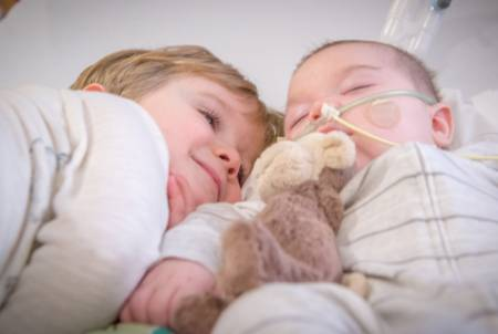 Felix and his brother Oscar cuddle in Gillette Children's PICU