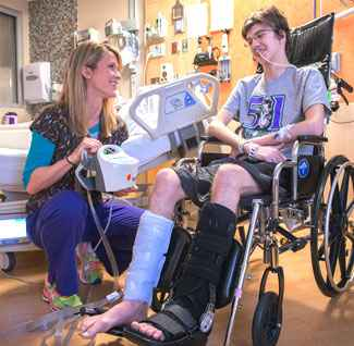 Patient in blue pneumoboot learns how it prevents thromboembolism.