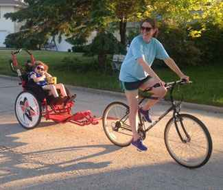 Kira, who has Rett syndrome, enjoys biking with her family.