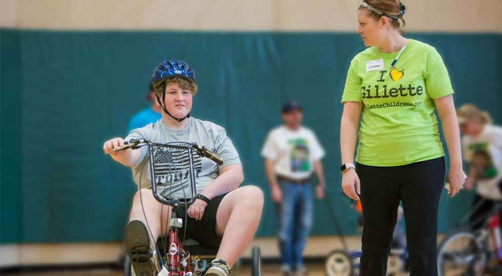 Gillette therapeutic recreation specialist working with a patient on adaptive bike