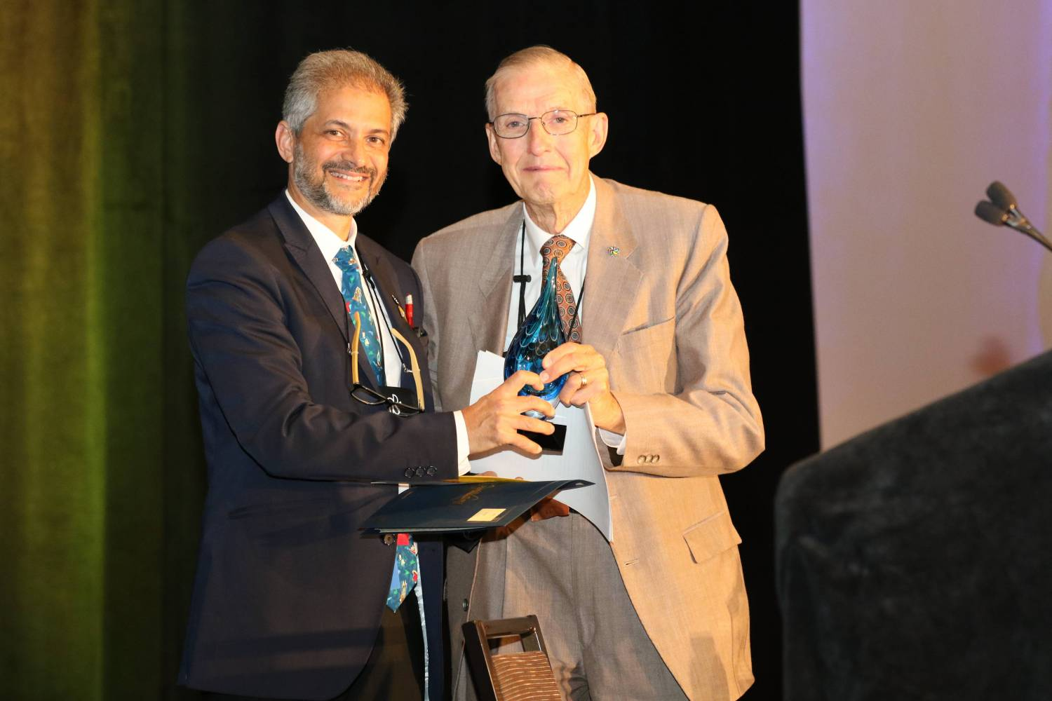 Jim Gage, MD, accepts his award from Unni Narayanan, president of the American Academy for Cerebral Palsy and Developmental Medicine.