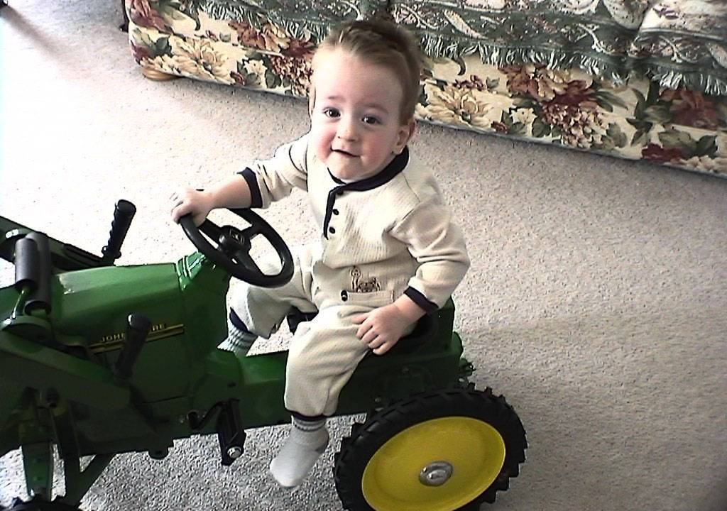 A young Connor rides his toy tractor.