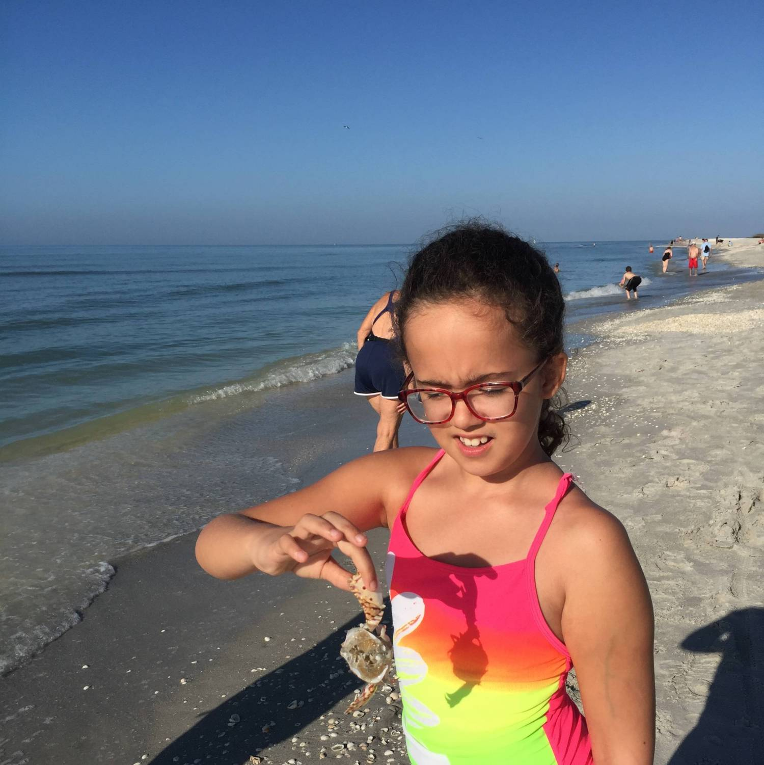 Maia, CP patient, pinches a crab to document her beach exploration.