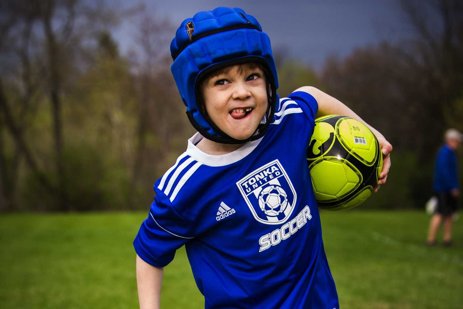 Gillette patient Ezra holds and runs with soccer ball