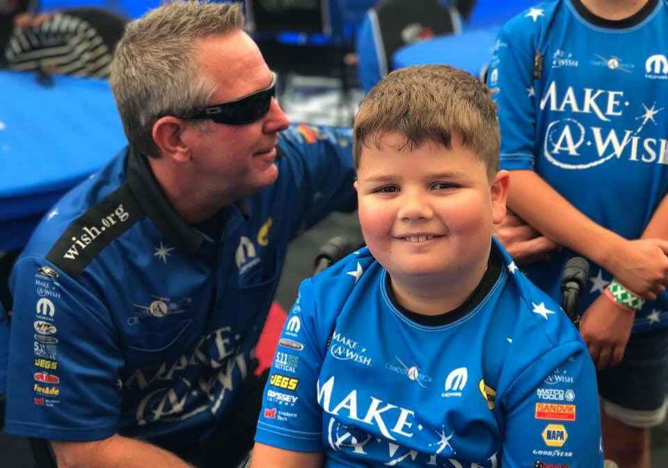 Caleb with Tommy Johnson Jr. he drives the Make A Wish race car.