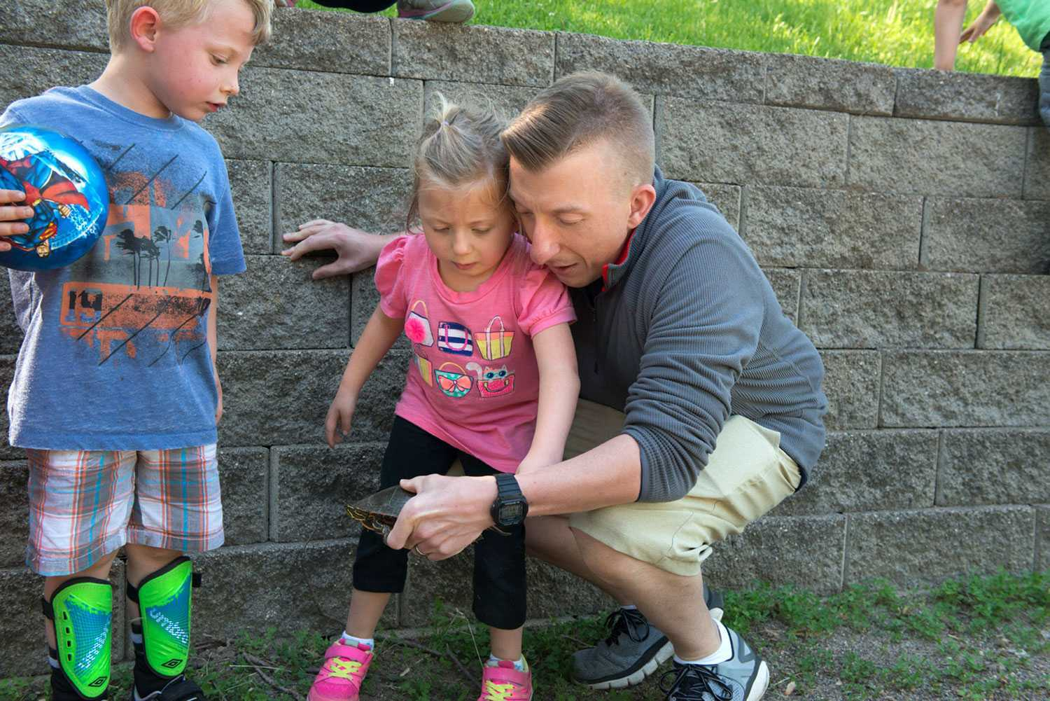 Hope, her brother Noah, and Kevin take a closer look at a turtle they discovered in a neighborhood park.
